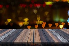 Empty wooden table or plank with heart love bokeh of light from road or street with city tower on background for product display. Copy space available stock photography