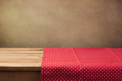 Empty wooden table with polka dots tablecloth. Over grunge background Stock Photo
