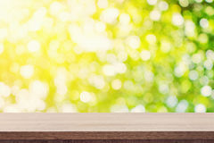 Empty wooden table for product placement or montage and green bo. Ken blurred background Royalty Free Stock Image