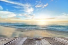 Empty wooden table with sea, sand beach and beautiful sunrise.  royalty free stock images