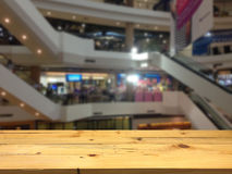 Empty wooden table space platform and blurred shopping mall back Stock Photo