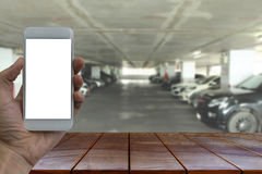 Empty wooden table space platform and Hand holding smartphone wi. Th white blank screen over blurred  Parking lot in the mall background for product display Stock Image