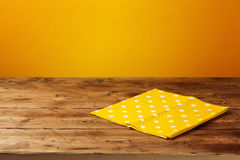 Empty wooden table with tablecloth over yellow background. Autumn season. Concept Stock Image