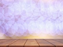 Empty wooden table top with abstract blurred lighting background stock images