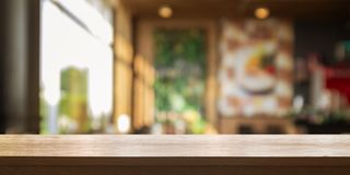 Empty wooden table top with blur coffee shop or restaurant inter. Ior background, Panoramic banner. Abstract background can be used product display royalty free stock photography