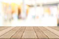 Empty wooden table top on blurred background at shopping mall Stock Image