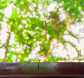 Empty wooden table top with blurred of fresh green nature Stock Photos