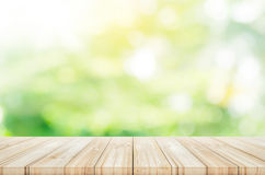 Empty wooden table top with blurred green garden background. Stock Image