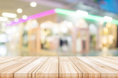 Empty wooden table top with blurred modern shopping mall backgro Royalty Free Stock Images