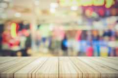 Empty wooden table top with blurred modern shopping mall backgro Stock Photo