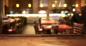 Empty wooden table top with blurred restaurant on background. Empty wooden table top with blurred restaurant and kitchen on background Stock Photos