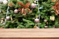 Empty wooden table top over Defocused of decorated Christmas tree with toys, gift box, lights, bauble inside the office building. royalty free stock image
