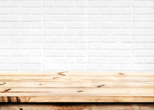 Empty wooden table with white brick wall background. Empty wooden table for product placement or montage with focus to the table top in the foreground, with stock photo