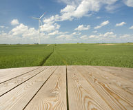 Empty wooden table on the wind-farm stock photos