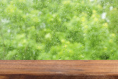 An empty wooden table by the window. Rain drops on the glass. Free place for creativity. Background. Royalty Free Stock Photos