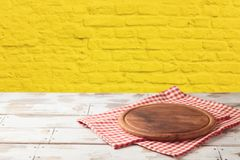 Free Empty Wooden Table With Pizza Board And Tablecloth Over Yellow Brick Stone Wall Background Stock Photo - 139561260