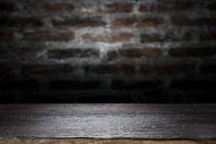 Wood table top on old dark brick wall background. Empty wooden table for your product display montage on old dark brick wall background Stock Photography