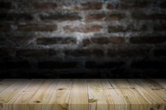 Wood table top on old dark brick wall background. Empty wooden table for your product display montage on old dark brick wall background Stock Photo