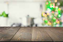 Empty wooden tabletop for display products and blurred kitchen with Christmas tree as background. Christmas table background with christmas tree in kitchen out stock images