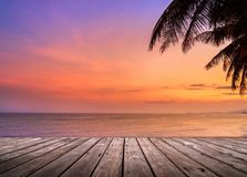 Wooden terrace over tropical island beach with coconut palm at sunset or sunrise time. Empty wooden terrace over tropical island beach with coconut palm at Stock Images