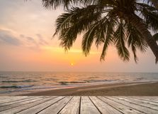 Wooden terrace over tropical island beach with coconut palm at sunset or sunrise time. Empty wooden terrace over tropical island beach with coconut palm at Royalty Free Stock Photos