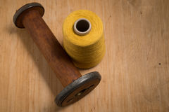 Empty Wooden Thread Spool Beside Yellow Thread Royalty Free Stock Photo