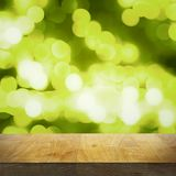 Empty wooden top table and bright blurred green background with lights and bokeh, focus on tabletop royalty free stock photography