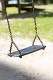 Empty wooden traditional swing on playground. Vertical crop in sunny day Royalty Free Stock Photos