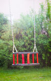 Empty wooden traditional swing on playground. Vertical crop in sunny day Stock Photo