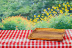 Empty wooden tray on red tablecloth over blur tree bokeh backgro Royalty Free Stock Images