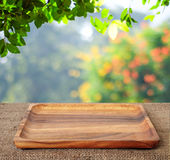 Empty wooden tray on table over blur trees background Royalty Free Stock Photos