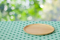 Empty wooden tray on table over blur trees with bokeh background Stock Photo