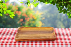 Empty wooden tray on table over blur trees with bokeh background Stock Photography