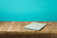 Empty wooden vintage table with tablecloth over blue wall background Royalty Free Stock Photography