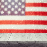 Empty wooden white table over USA flag bokeh background. USA national holidays background. 4th of July celebration. Royalty Free Stock Photography