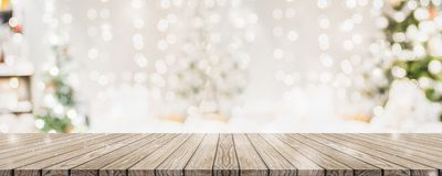Empty woooden table top with abstract warm living room decor with christmas tree string light blur background with snow,Holiday