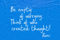 Empty worrying blue Rumi. Be empty of worrying. Think of who created thought - ancient Persian poet and philosopher Rumi quote handwritten on blue wall Stock Images
