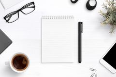 Empty writing pad on office desk surrounder with office supplies royalty free stock images