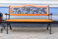 An empty wrought iron bench with wood accents against blue walls Royalty Free Stock Photo