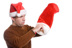 Empty Xmas Sock. A young man wearing a Santa hat is dumping out his Xmas sock, isolated against a white background Stock Photography