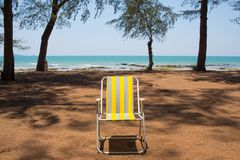 An empty yellow beach chair put by the pine tree beach showing breezy weather. An empty yellow beach chair put on the sand beach around with pine tree showing royalty free stock photo