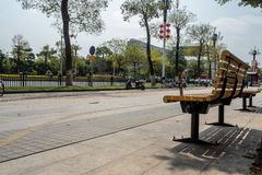 Empty yellow bench under the tree on pedestrian beside the street in midtown royalty free stock photo