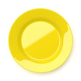 Empty yellow ceramic round plate isolated on white Royalty Free Stock Images