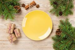 Empty yellow matte plate on wooden background. with christmas decoration, Round dish. New Year concept.  stock photos
