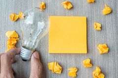 Empty yellow note and crumbled paper with Businessman holding lightbulb on wooden table background. New Idea, Creative, Innovation. Imagination, inspiration stock photo