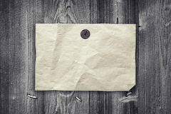 Empty yellow paper ad hanging on gray wooden wall Stock Photos