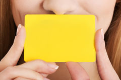 Empty yellow personal card over woman's face. Royalty Free Stock Photography