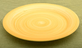 Empty yellow plate on green background Royalty Free Stock Photography