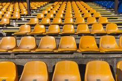 Empty yellow seats at sports stadium Stock Photo