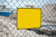 Empty yellow sign on construction site fence - warning sign mock-up.  royalty free stock image